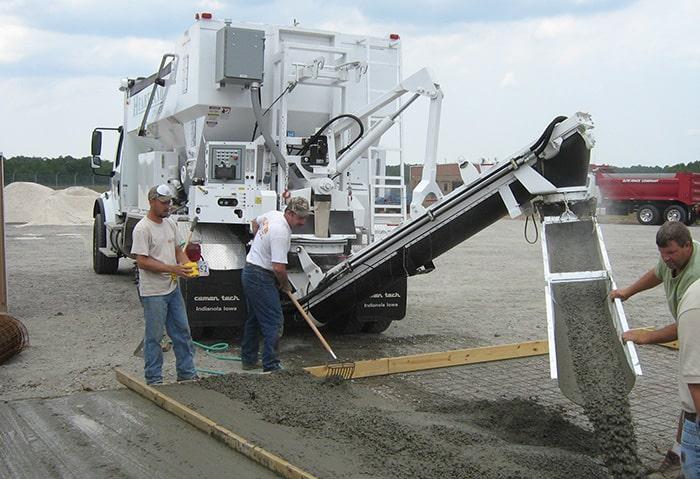 Volumetric mixer pouring concrete for parking lot.