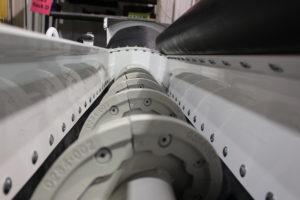 Wear blades line a volumetric mixer assembly.
