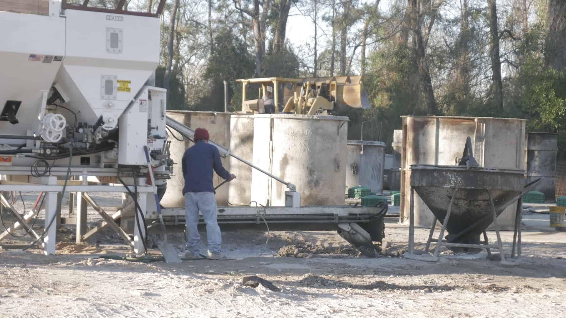 Stationary concrete mixer pouring aerobic septic tanks.