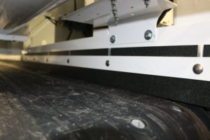 A side guide sits parallel to the conveyor belt inside a mobile concrete mixer.
