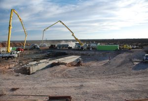 Volumetric mixers work with concrete pumps on a large job site.