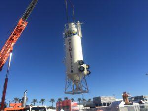 A crane lifts an upright bulk cement silo.