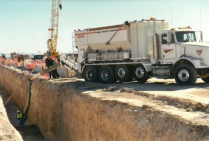 A mobile concrete mixer fills a tunnel with flowable fill.