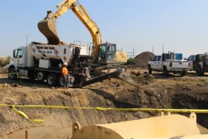 A volumetric concrete mixer pours continuous flowable fill to backfill a trench.