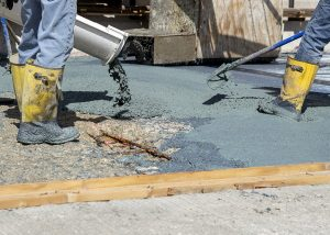 Latex modified concrete pours from a volumetric mixer to a bridge deck on Interstate 55 in Illinois.