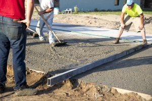 A finishing crew smooths poured concrete with the appropriate water/cement ratio for a business parking lot.